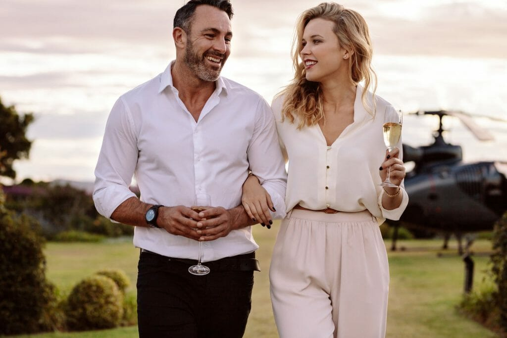 Man and woman of high net worth walking away from their helicopter while drinking champagne